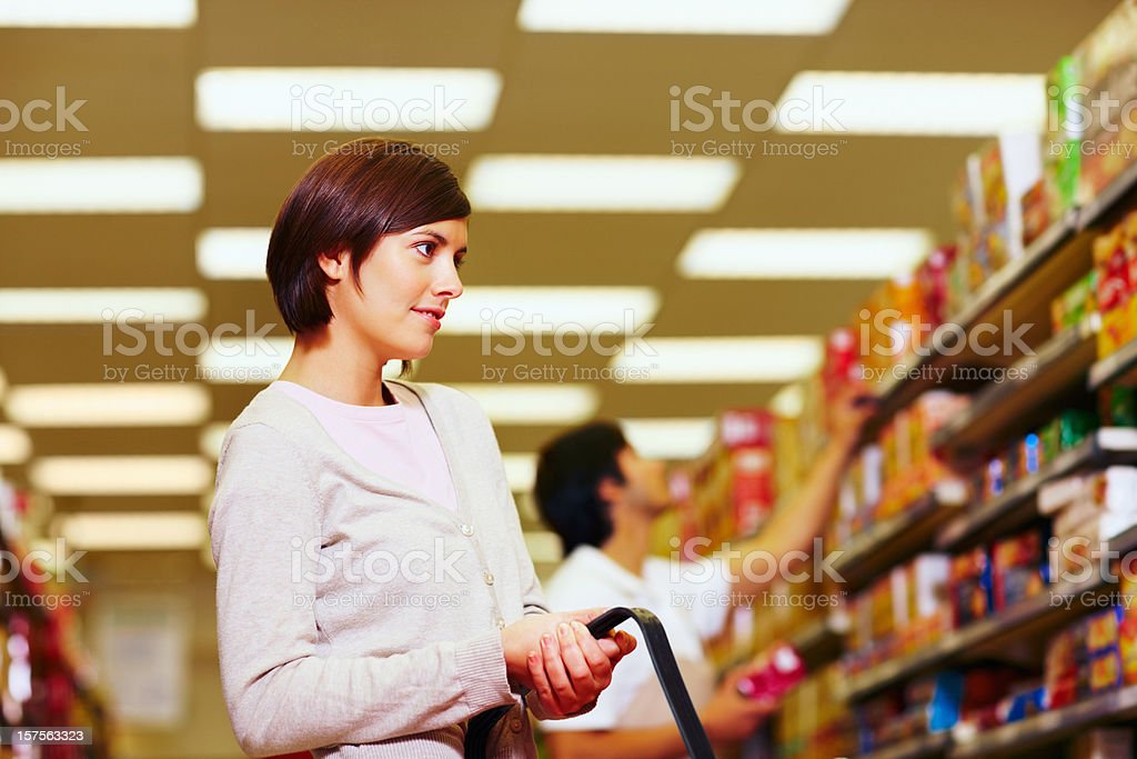 Woman looking for product on supermarket shelf royalty-free stock photo