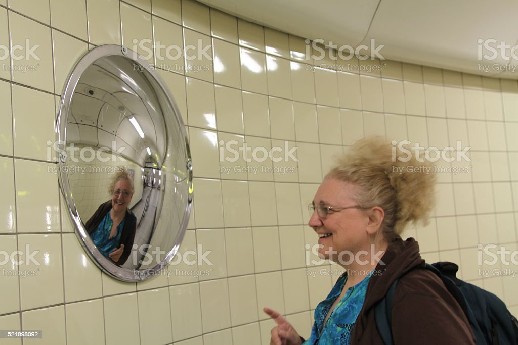Woman Looking In A Convex Mirror stock photo
