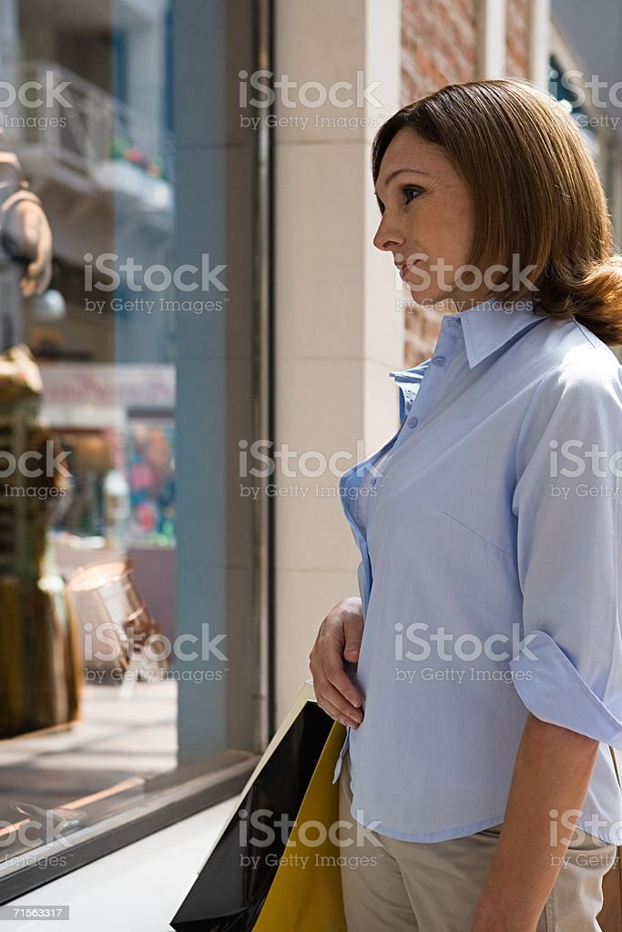 Woman looking in a shop window stock photo