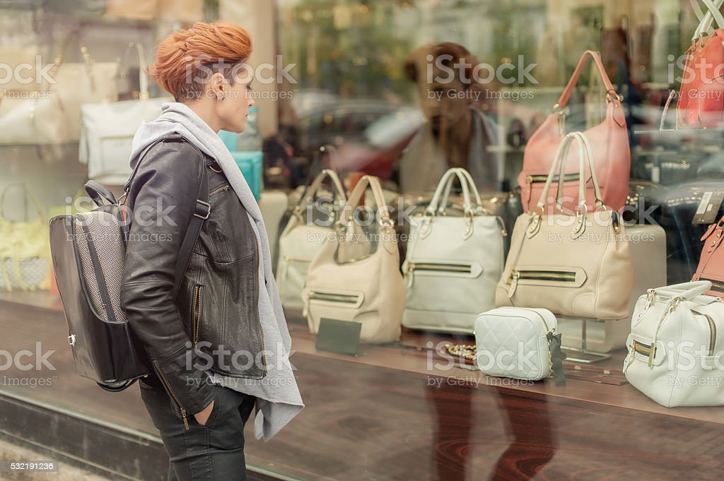 Woman looking in a shop window with handbags stock photo