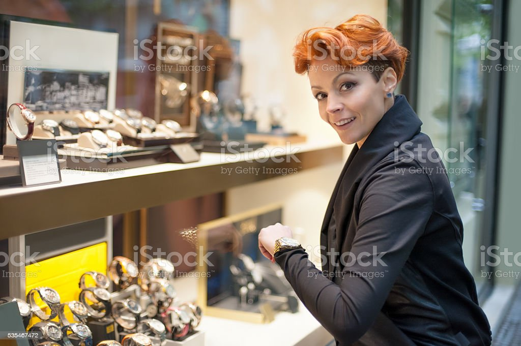 Woman looking in a shop window with watches stock photo