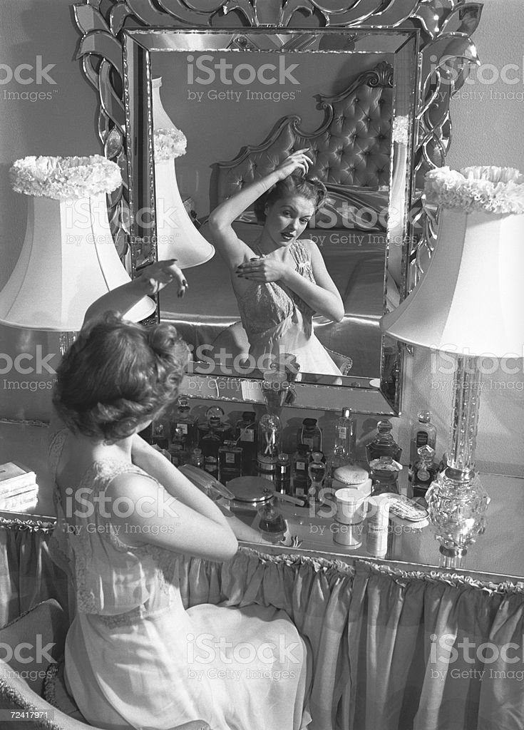 Woman looking in mirror, checking underarms (B&W) stock photo