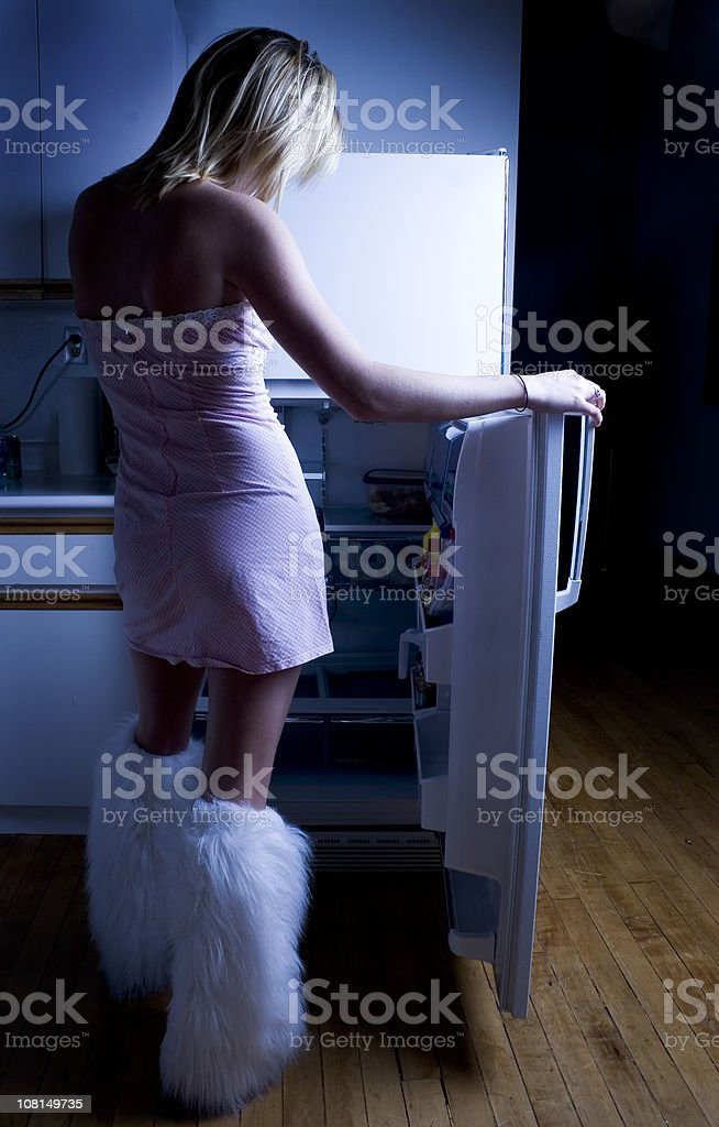 Woman Looking in Refrigerator at Night royalty-free stock photo