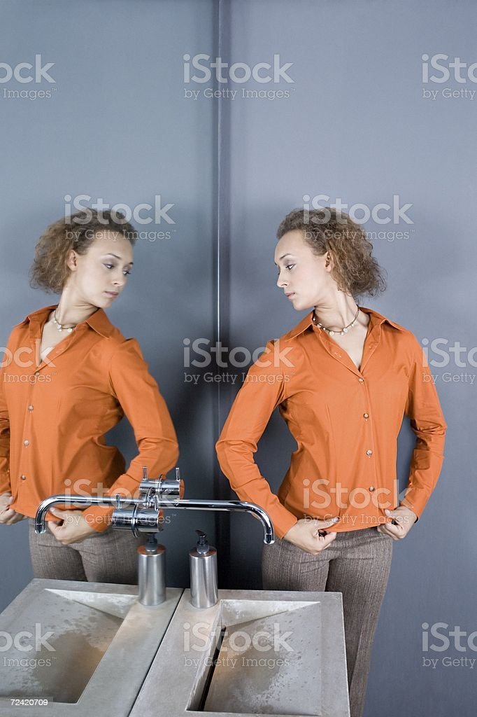 Woman looking in restroom mirror royalty-free stock photo