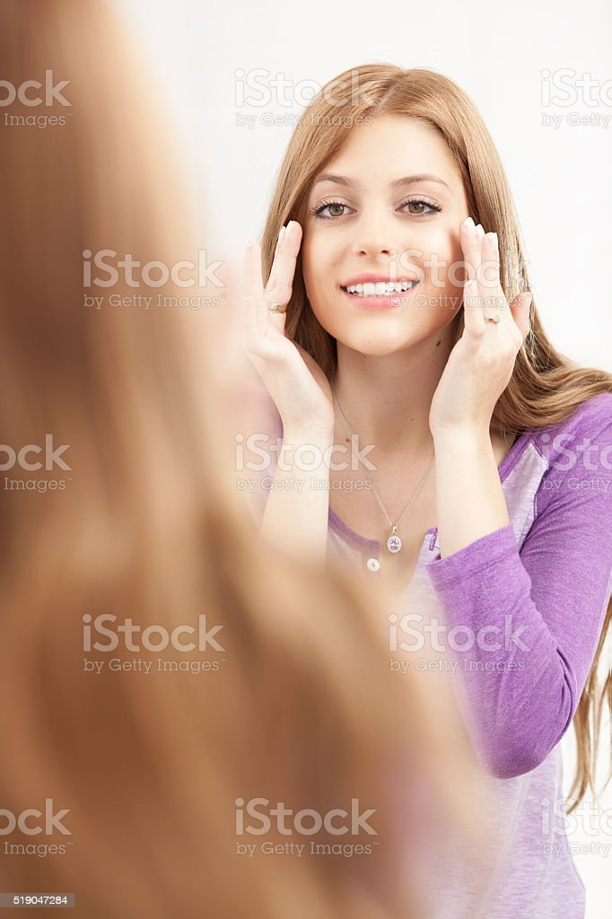 Woman looking in the mirror after beauty treatment. stock photo