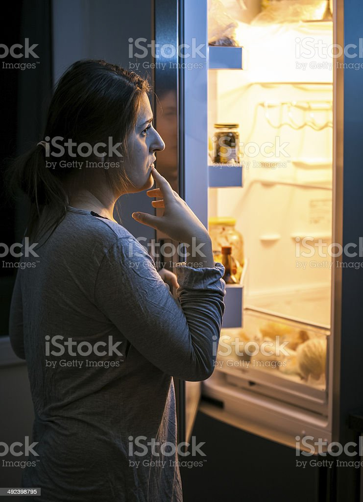 woman looking in the refrigerator at late evening stock photo