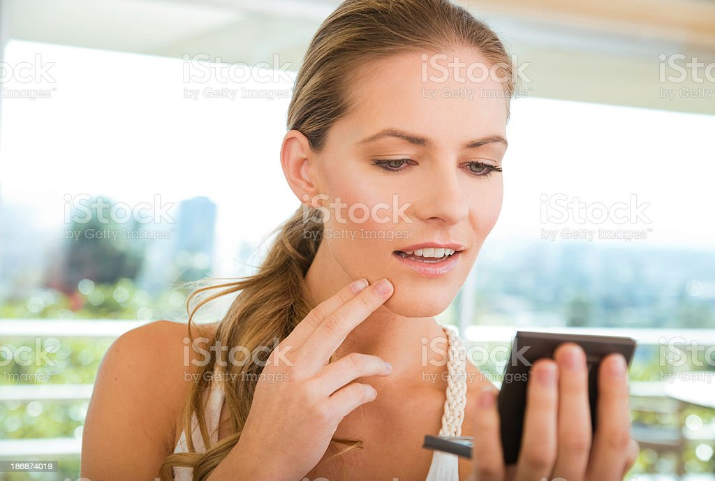 Woman looking into a compact mirror stock photo