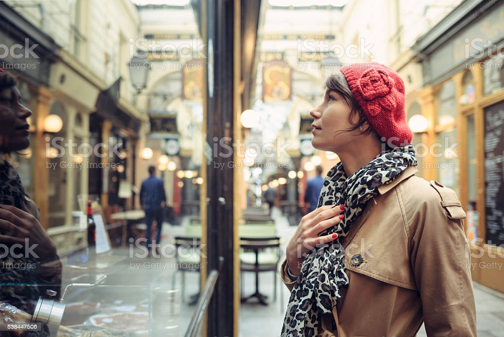 Woman looking into window of traditional store in Paris. stock photo