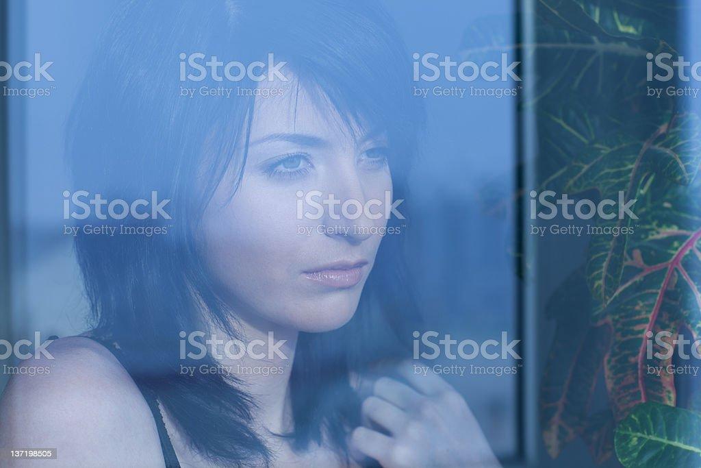 woman looking into window stock photo