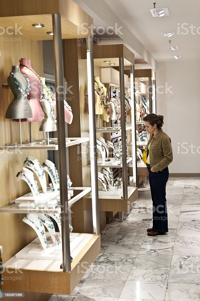 Woman looking items in a costume jewelry case royalty-free stock photo