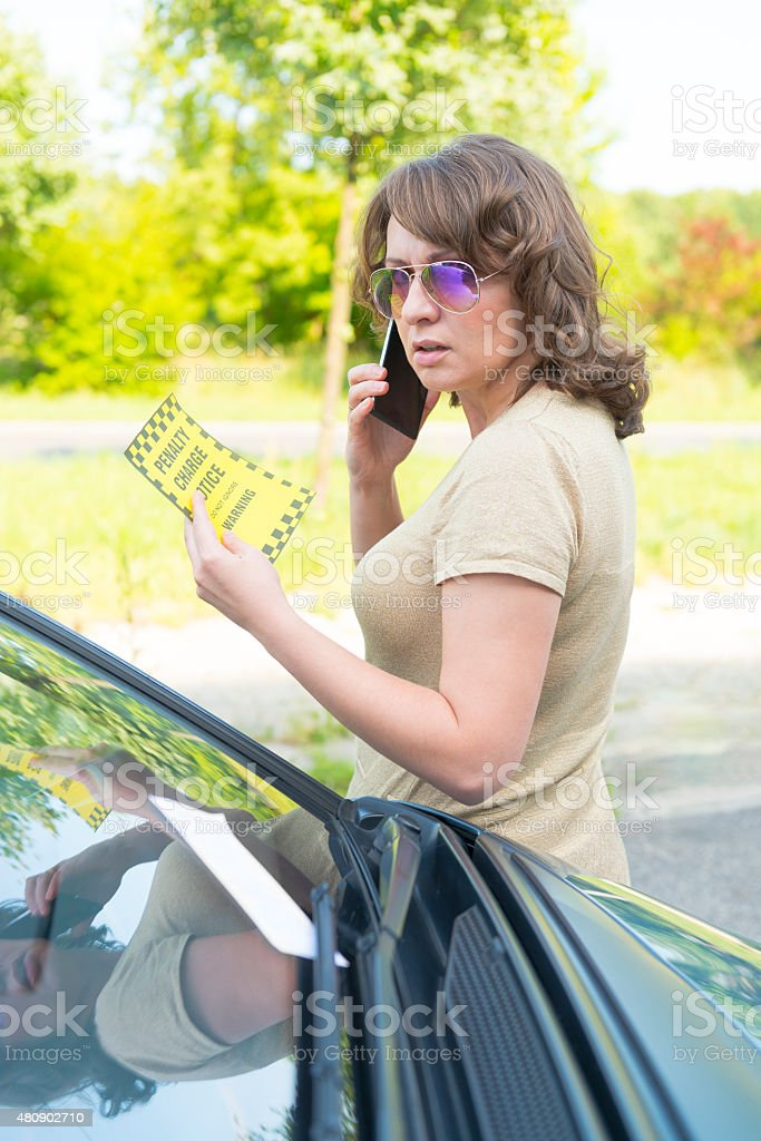 woman looking on parking ticket stock photo