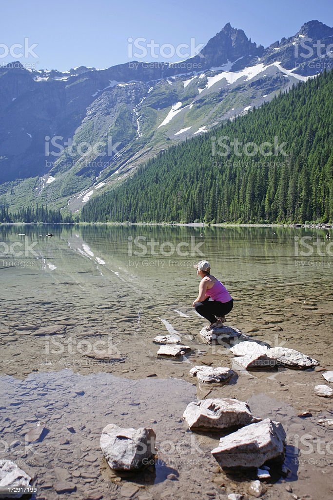 Woman looking out at Avalanche Lake in Glacier National Park royalty-free stock photo