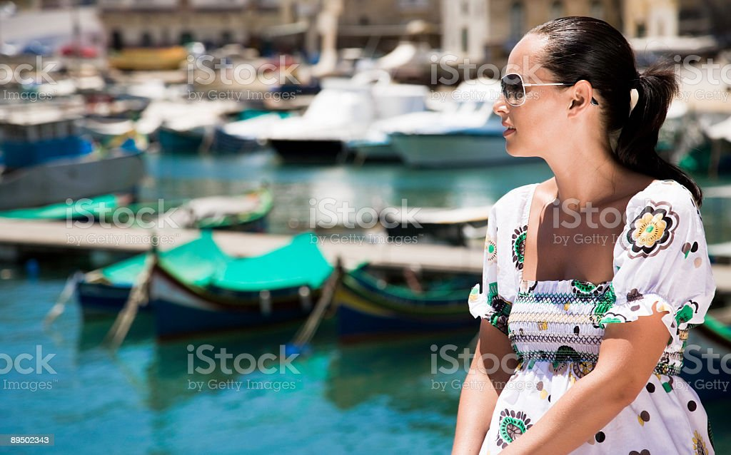 Woman looking out at harbour stock photo