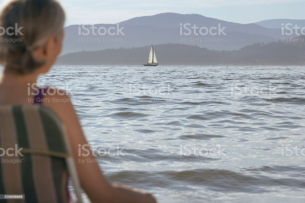 Woman looking out at the ocean stock photo