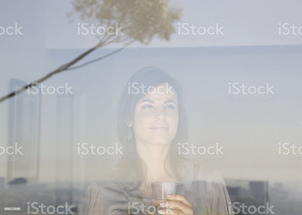 Woman looking out living room window stock photo