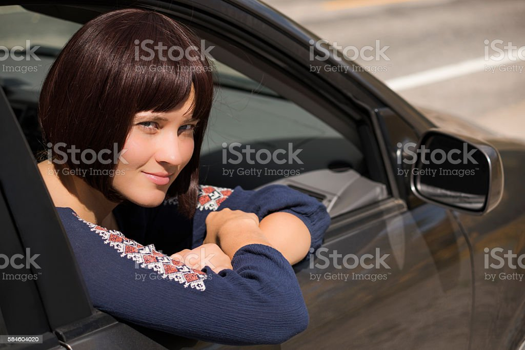 Woman looking out of passanger window of car smiling stock photo