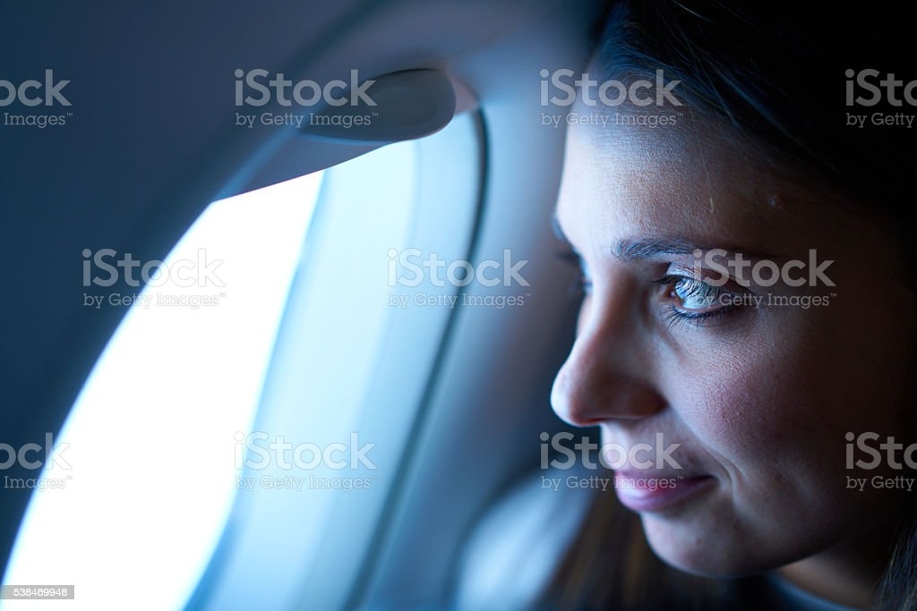 woman looking out of window of airplane stock photo