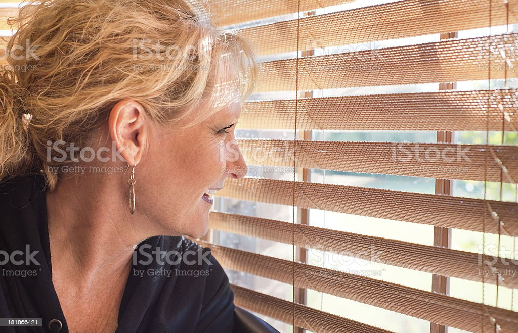Woman looking out window blinds royalty-free stock photo