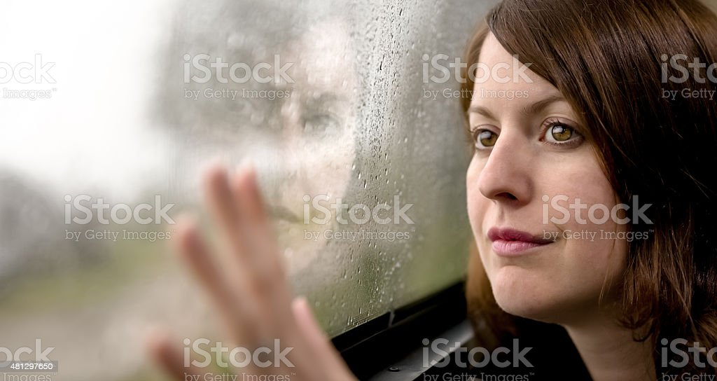 Woman looking outside on Rainy Day stock photo