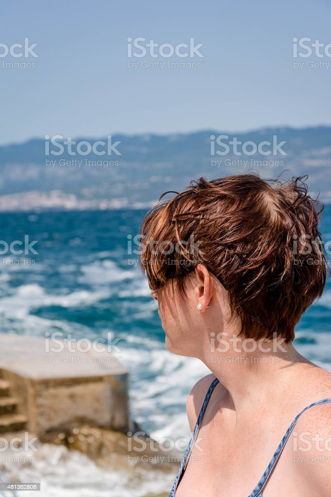 Woman looking rough sea stock photo