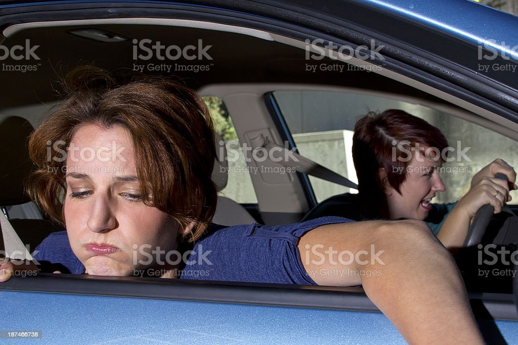 Woman looking sick with head out the blue car window stock photo