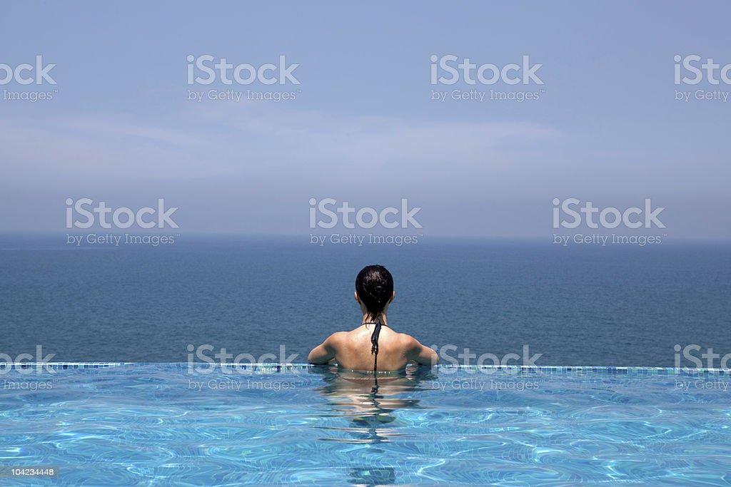 woman looking the sea bathing  infinity swimming  pool stock photo