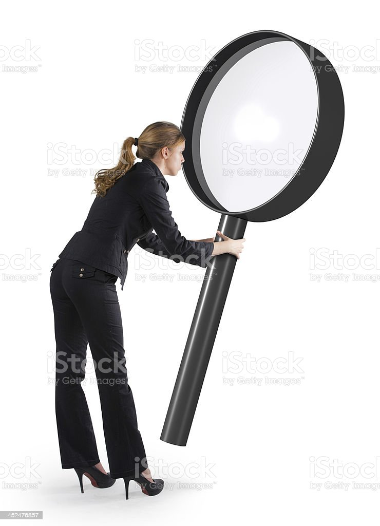 Woman looking through a giant magnifying glass stock photo
