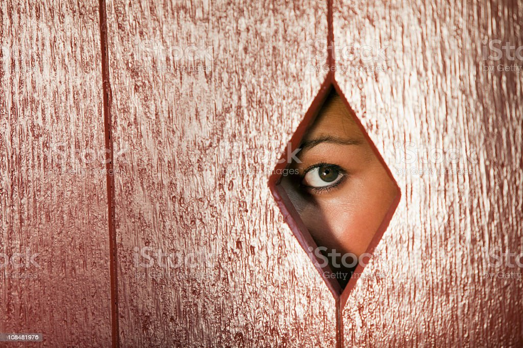 Woman Looking Through a Hole in the Wall royalty-free stock photo