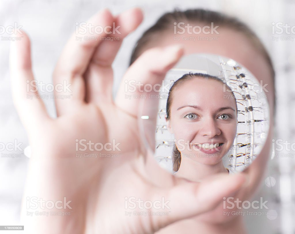 Woman looking through a lens stock photo