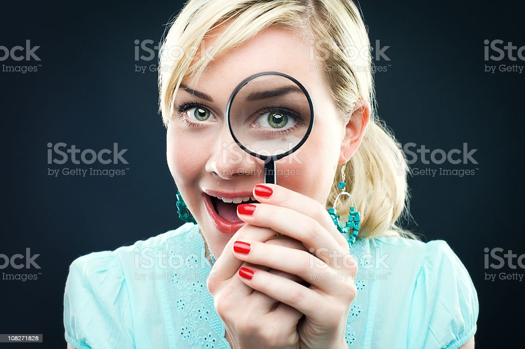 Woman looking through a magnifying glass stock photo