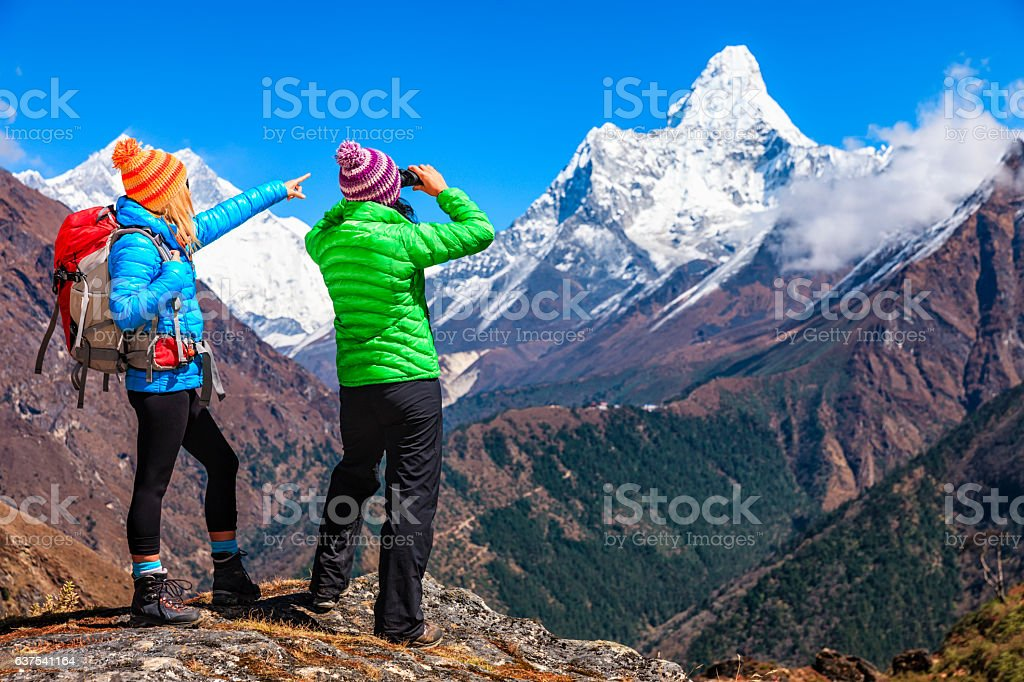 Woman looking through binoculars at Ama Dablam, Mount Everest Region stock photo