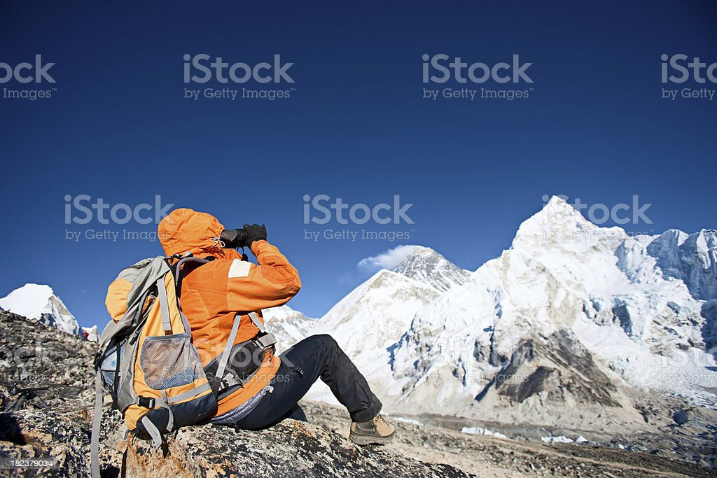 Woman looking through binoculars at Mount Everest royalty-free stock photo