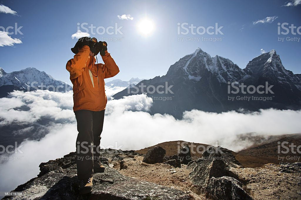 Woman looking through binoculars, Cholatse and Taboche on background royalty-free stock photo