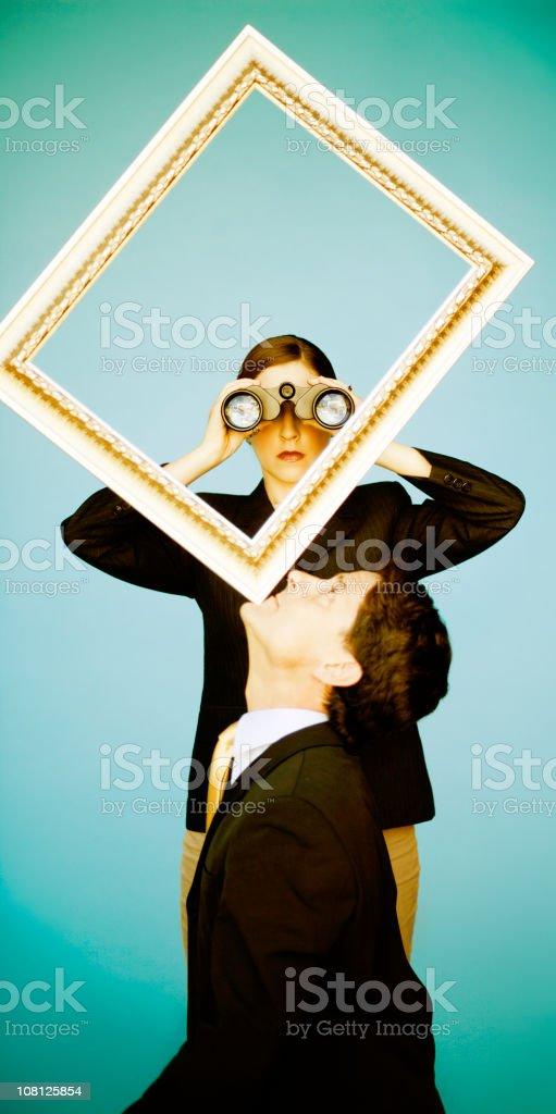 Woman Looking Through Binoculars, Man Balancing Frame on Head royalty-free stock photo
