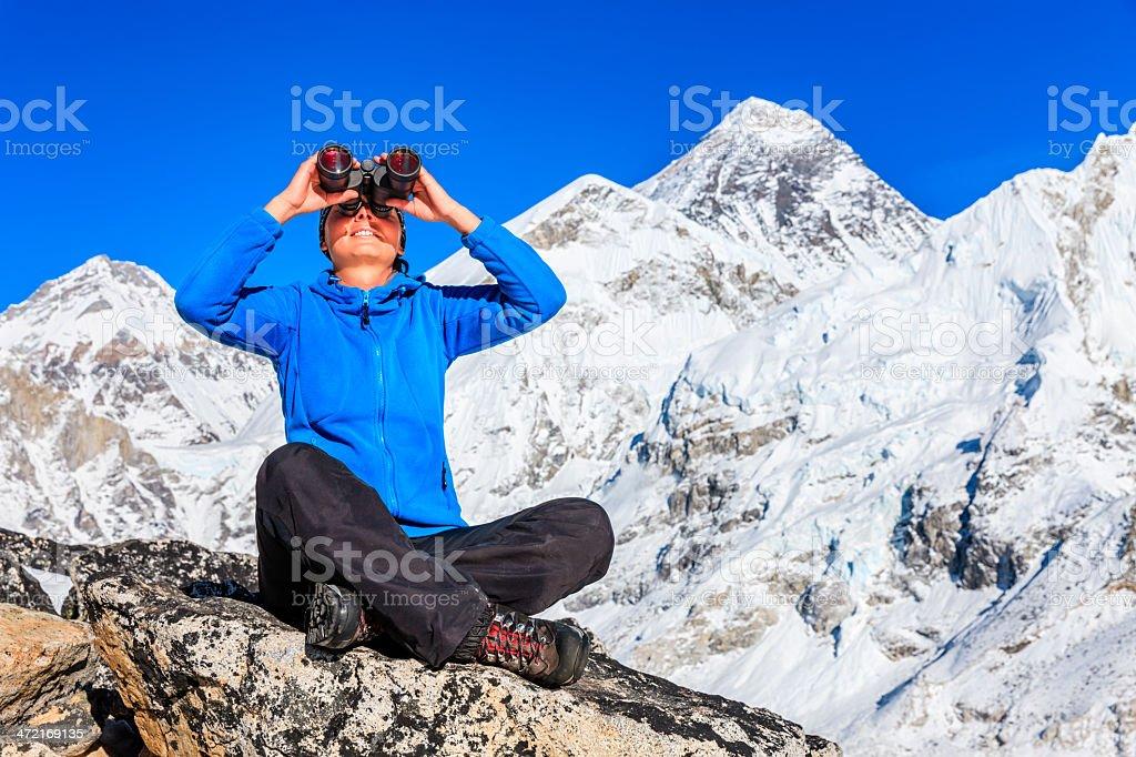 Woman looking through binoculars, Mount Everest on background royalty-free stock photo