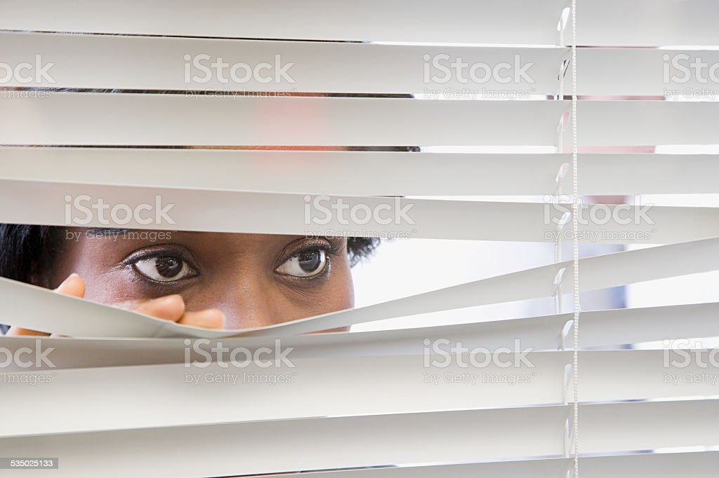 Woman looking through blinds stock photo