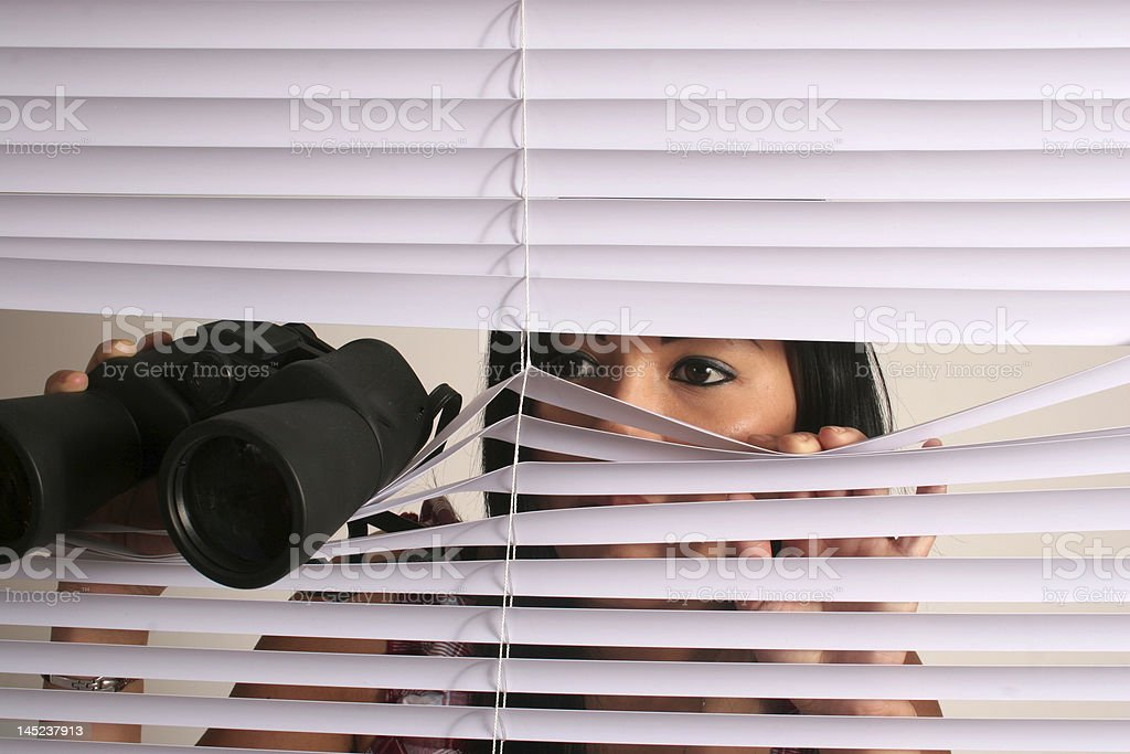 Woman looking through blinds with binoculars stock photo