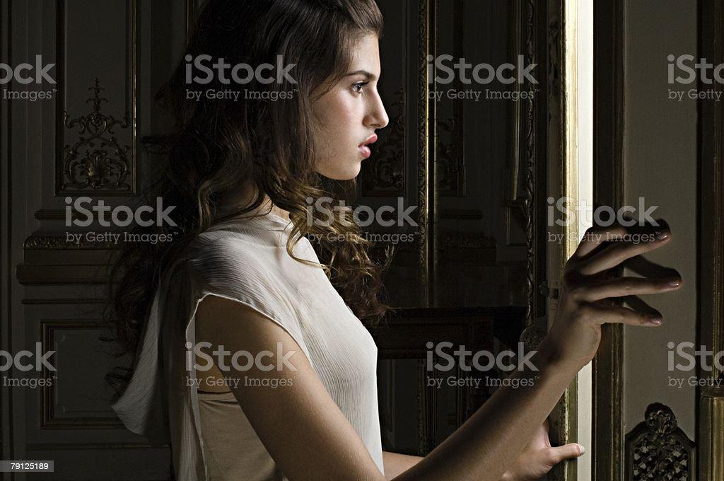 Woman looking through doorway royalty-free stock photo