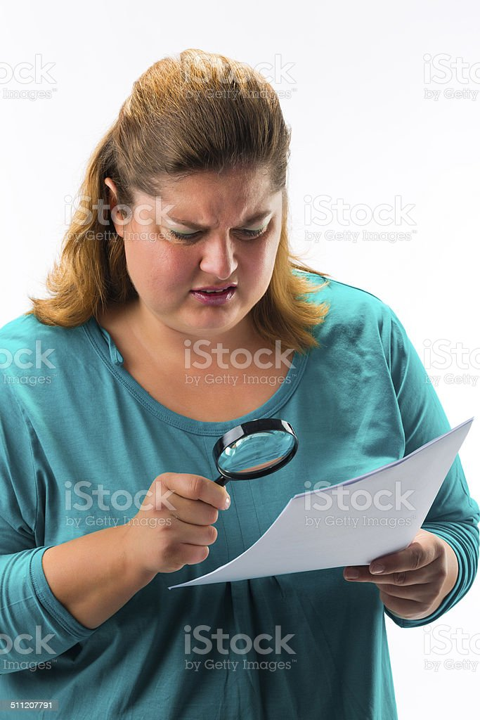 Woman looking through magnifying glass or loupe stock photo