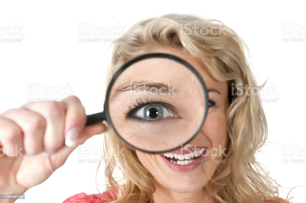 woman looking through magnifying glass with huge eye royalty-free stock photo