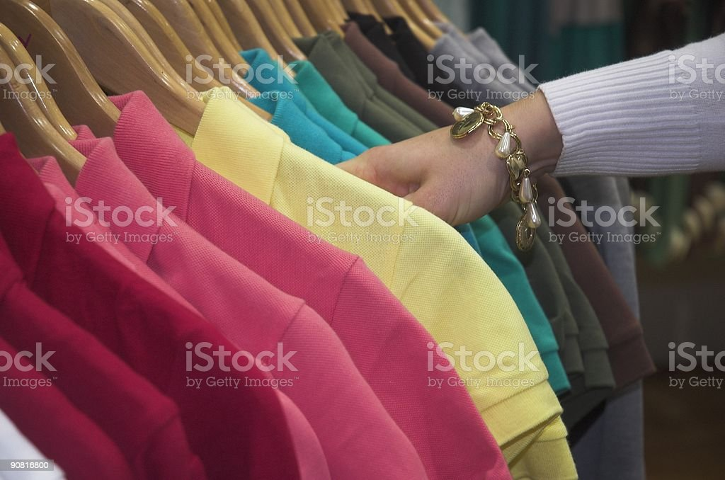 Woman looking through many colors of collared shirts stock photo