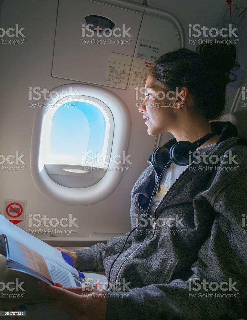 Woman looking through plane window stock photo