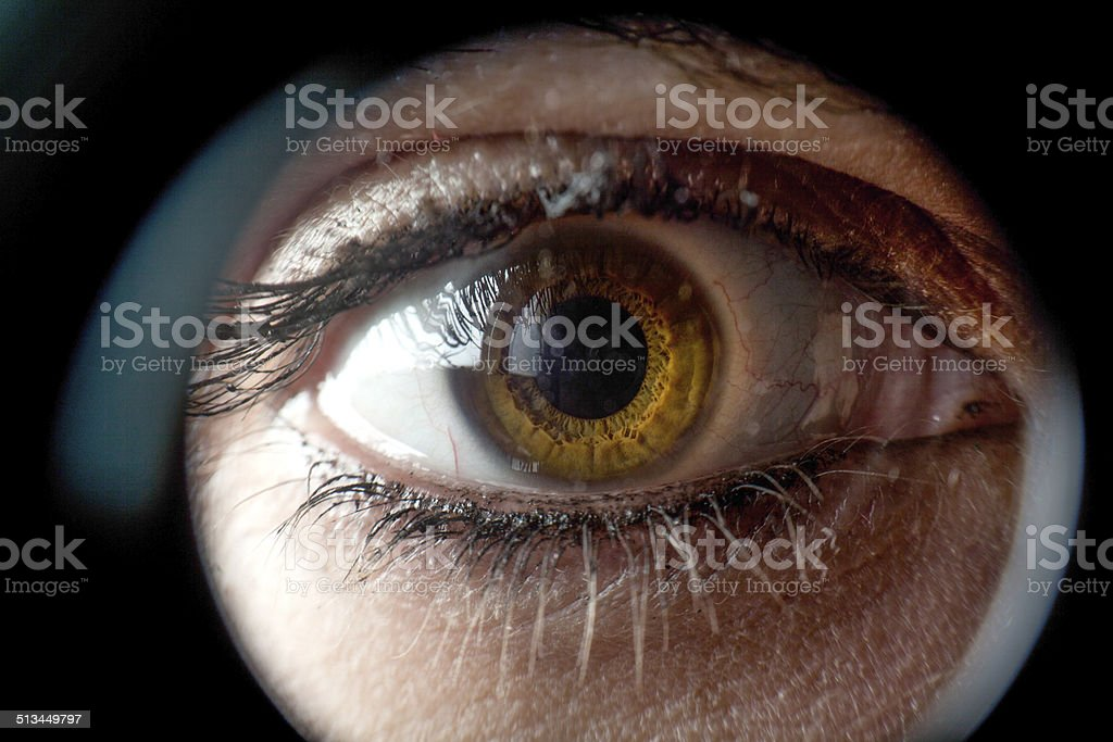 Woman looking through spyhole stock photo