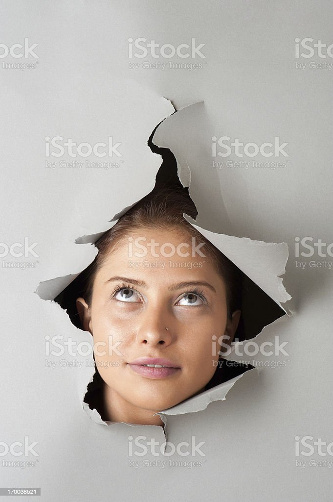 Woman looking through torn paper royalty-free stock photo