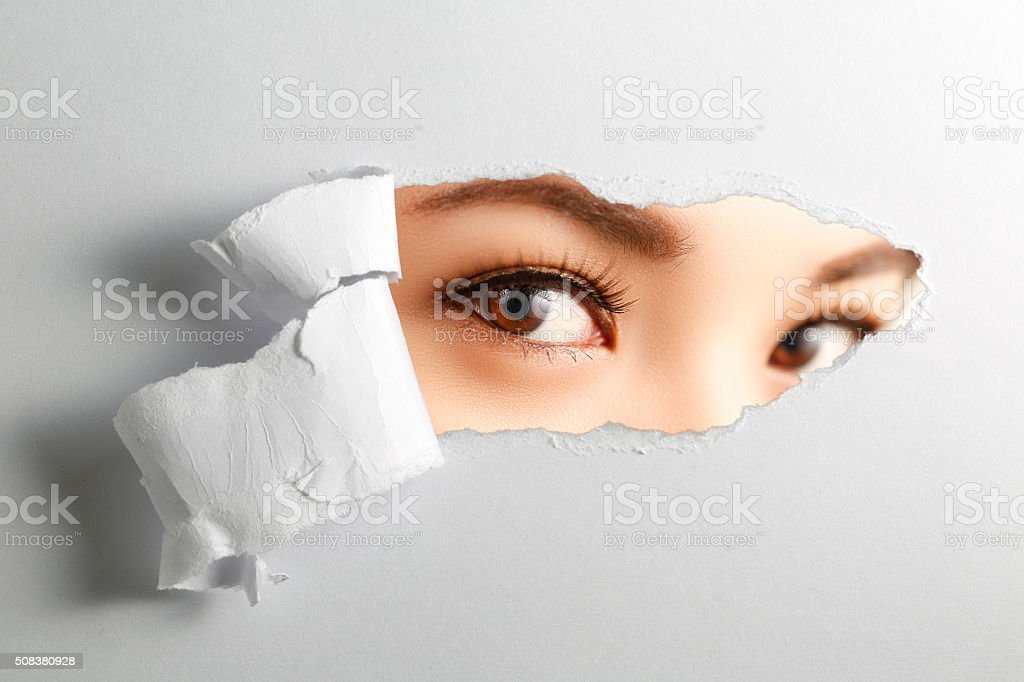 woman looking through torn paper stock photo