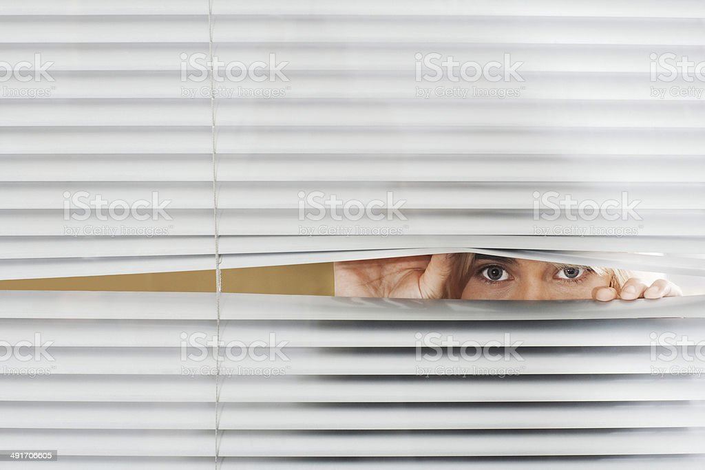 Woman Looking Through Venetian Blinds stock photo