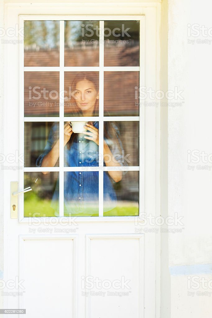 Woman looking through window of french door and drinking coffee stock photo