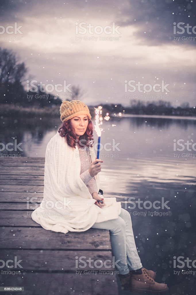 Woman looking to the lake,holding sparkles stock photo