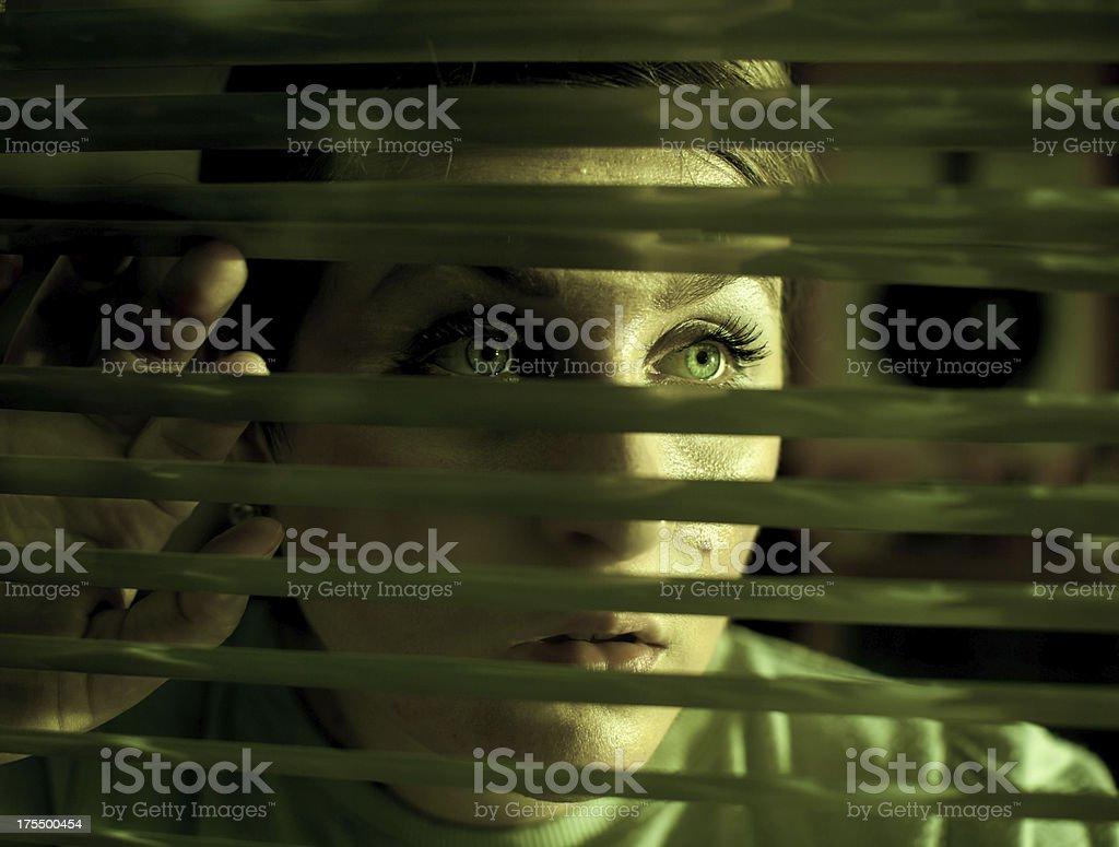 Woman looking trough window stock photo