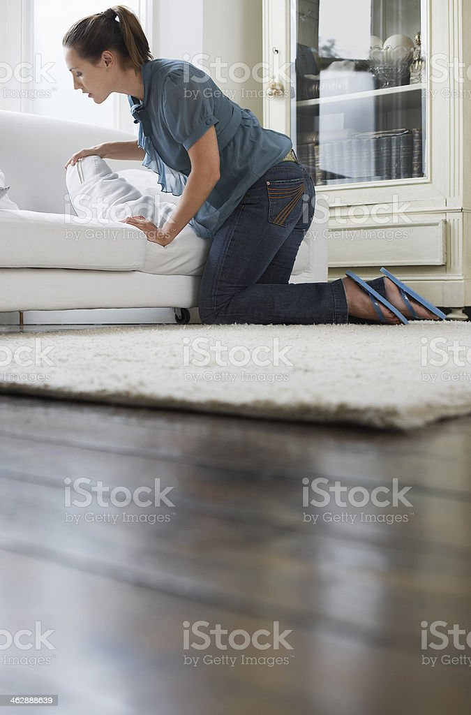 Woman looking under cushions of sofa stock photo